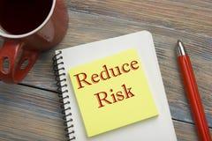 Estratégias de gestão de riscos - evite, explore, transfira, aceite, reduza, ignore Tabela da mesa de escritório com caderno, pen fotos de stock