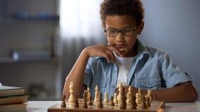 Estrategia concentrada del ajedrez del muchacho que se convierte, jugando al juego de mesa con el amigo fotos de archivo