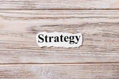 Estrategia de la palabra en el papel Concepto Palabras de la estrategia en un fondo de madera Imagenes de archivo