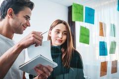 Estrategia empresarial prepearing coworking inteligente de la gente y fijado en una pared de cristal pegajosa de la nota fotos de archivo