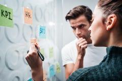 Estrategia empresarial prepearing coworking inteligente de la gente y fijado en una pared de cristal pegajosa de la nota foto de archivo libre de regalías