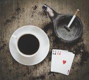 Estratto del gioco: tazza di caffè, portacenere con la sigaretta e quattro carte da gioco degli assi Fotografie Stock Libere da Diritti