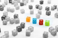 Estratto di amore I piccoli cubi variopinti isolati hanno sparso su fondo bianco Fotografie Stock