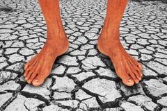 Estratto, piede dell'uomo anziano che sta sulla crepa della terra Immagine Stock