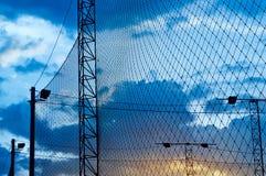 Estratto, siluetta variopinta della lampada e rete intorno a calcio del campo nel tramonto blu Fotografia Stock