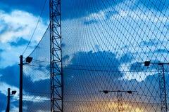 Estratto, siluetta variopinta di rete intorno a calcio del campo nel tramonto blu Fotografie Stock