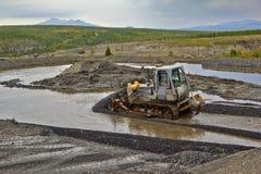 Estrazione dell'oro in Susuman Il bulldozer e il derocker fotografie stock libere da diritti