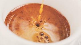 Estrazione di caffè espresso con il crema ricco in tazza fotografia stock