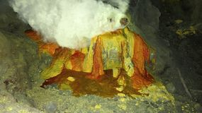Estrazione mineraria cruda dello zolfo nel cratere del vulcano attivo di Kawah Ijen su Java fotografia stock