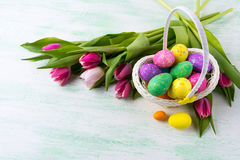 A estrela da Páscoa decorou ovos do brilho no backg amarelo da cesta de vime Fotos de Stock