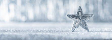 Estrela de prata brilhante do Natal com luzes de Natal defocused no fundo Bandeira do Natal fotografia de stock