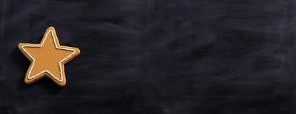 A estrela deu forma à cookie do pão-de-espécie, vista superior, quadro-negro, bandeira fotografia de stock royalty free