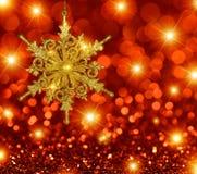 A estrela do floco de neve do ouro no vermelho Stars o fundo Imagem de Stock Royalty Free