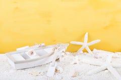 Estrela do mar com o barco do brinquedo no fundo amarelo imagens de stock