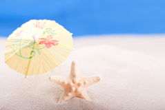 Estrela do mar na praia sob um guarda-chuva Foto de Stock Royalty Free