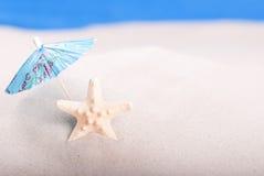 Estrela do mar na praia sob um guarda-chuva Foto de Stock
