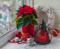 Estrela do Natal (pulcherrima do eufórbio) na janela e no Cristo Foto de Stock