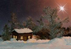 Estrela do Natal sobre a casa na neve e nos abetos Imagem de Stock Royalty Free