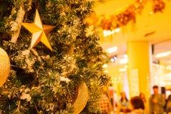 Estrela do ouro, crescente e fundo de brilho de suspensão das quinquilharias da bola com a árvore de Natal nevado decorada do inv fotos de stock royalty free