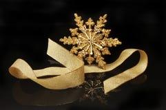 Estrela e fita do Natal do ouro contra o preto Fotos de Stock Royalty Free