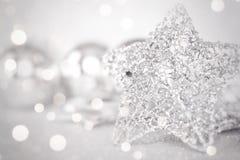 Estrela e ornamento de prata brilhantes no bokeh abstrato brilhante do fundo Foto de Stock Royalty Free