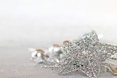 Estrela e ornamento de prata brilhantes no bokeh abstrato brilhante do fundo Imagens de Stock Royalty Free