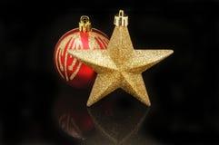 Estrela e quinquilharia do Natal contra o preto Foto de Stock