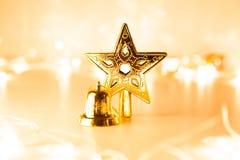 Estrela e sino de brilho dourados do Natal no backgro claro de Bokeh Fotos de Stock
