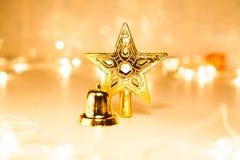 Estrela e sino de brilho dourados do Natal no backgro claro de Bokeh Imagem de Stock