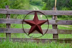 Estrela rústica de Texas na cerca de madeira do lado do campo, com a estrada à casa que dissolve-se lentamente no fundo ilustração royalty free