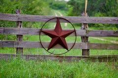 Estrela rústica de Texas na cerca de madeira do lado do campo, com a estrada à casa que dissolve-se lentamente no fundo ilustração stock
