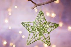 Estrela tecida de brilho do laço do ornamento do Natal que pendura no ramo de árvore Garland Lights Pastel Color Background eferv Fotos de Stock