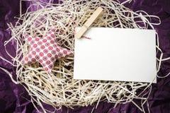 Estrela vermelha do brinquedo e cartão vazio na palha imagens de stock
