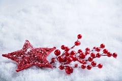 Estrela vermelha do vintage mágico bonito em um fundo branco da neve Conceito do inverno e do Natal Fotografia de Stock