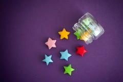Estrelas afortunadas do origâmi colorido que derramam fora de um frasco Imagens de Stock