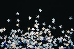 Estrelas brilhantes da folha no fundo preto Confetti festivo imagens de stock royalty free