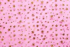 Estrelas do ouro na matéria têxtil cor-de-rosa Fotografia de Stock Royalty Free