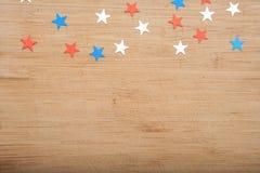 Estrelas dos confetes no fundo de madeira 4 de julho, o Dia da Independência, cartão, convite nos EUA embandeira cores Vista da p Imagem de Stock Royalty Free