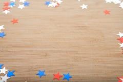 Estrelas dos confetes no fundo de madeira 4 de julho, o Dia da Independência, cartão, convite nos EUA embandeira cores Vista da p Imagem de Stock