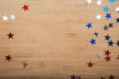 Estrelas dos confetes no fundo de madeira 4 de julho, o Dia da Independência, cartão, convite nos EUA embandeira cores Vista da p Fotos de Stock Royalty Free