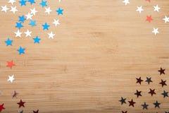 Estrelas dos confetes no fundo de madeira 4 de julho, o Dia da Independência, cartão, convite nos EUA embandeira cores Vista da p Fotografia de Stock