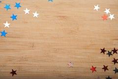 Estrelas dos confetes no fundo de madeira 4 de julho, o Dia da Independência, cartão, convite nos EUA embandeira cores Vista da p Imagens de Stock
