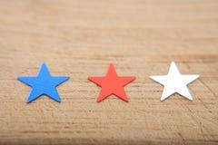 Estrelas dos confetes no fundo de madeira 4 de julho, o Dia da Independência, cartão, convite nos EUA embandeira cores Vista da p Fotografia de Stock Royalty Free