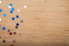 Estrelas dos confetes no fundo de madeira 4 de julho, o Dia da Independência, cartão, convite nos EUA embandeira cores Vista da p Foto de Stock