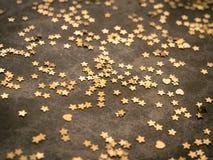 Estrelas douradas no fundo do marrom escuro fotografia de stock