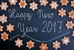 Estrelas e flocos de neve das cookies do Natal do pão-de-espécie com ano novo feliz 2017 do texto no fundo preto Fotos de Stock