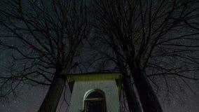 Estrelas que giram sobre a capela e a silhueta das limeiras no céu noturno, lapso de tempo da astronomia, tiro da zorra, filme