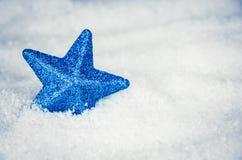 Estrella azul que brilla intensamente en nieve Fotografía de archivo