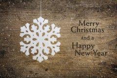 Estrella blanca del copo de nieve que cuelga sobre un fondo de madera rústico Imagenes de archivo