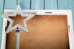 Estrella brillante de la Navidad con el marco azul, el espacio del texto y el fondo de madera Fotos de archivo
